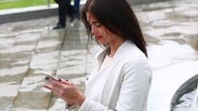 Ritratto della ragazza che ride facendo uso dello smartphone Giovane donna graziosa con il suo telefono cellulare sul fondo della stock footage