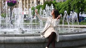 Ritratto della ragazza che ride facendo uso dello smartphone Giovane donna graziosa con il suo telefono cellulare sul fondo della archivi video