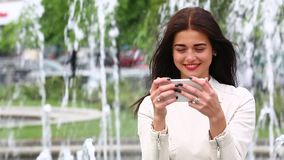 Ritratto della ragazza che ride facendo uso dello smartphone Giovane donna graziosa con il suo telefono cellulare sul fondo della video d archivio