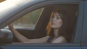 Ritratto della ragazza che si siede in automobile sul sedile del ` s dell'autista sul fondo di tramonto video d archivio
