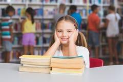 Ritratto della ragazza che si siede con il mucchio dei libri in biblioteca Fotografia Stock