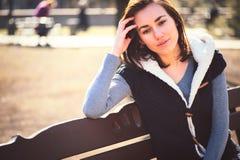 Ritratto della ragazza che si siede su un banco immagini stock
