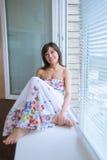 Ritratto della ragazza che si siede sul davanzale Fotografia Stock