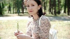 Ritratto della ragazza che si siede sull'erba che tiene un fiore e che guarda in camera archivi video