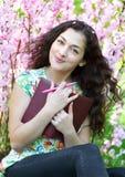 Ritratto della ragazza che si siede vicino al cespuglio con i fiori rosa e che legge il libro Immagini Stock