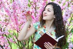 Ritratto della ragazza che si siede vicino al cespuglio con i fiori rosa e che legge il libro Immagini Stock Libere da Diritti