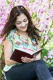 Ritratto della ragazza che si siede vicino al cespuglio con i fiori rosa e che legge il libro Immagine Stock