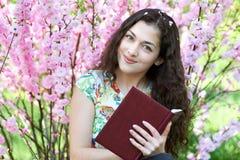 Ritratto della ragazza che si siede vicino al cespuglio con i fiori rosa e che legge il libro Fotografie Stock