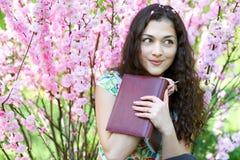 Ritratto della ragazza che si siede vicino al cespuglio con i fiori rosa e che legge il libro Fotografie Stock Libere da Diritti