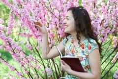 Ritratto della ragazza che si siede vicino al cespuglio con i fiori rosa e che legge il libro Immagine Stock Libera da Diritti