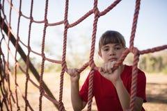 Ritratto della ragazza che sta rete vicina durante la corsa ad ostacoli fotografia stock libera da diritti