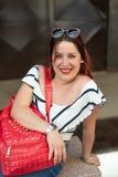 Ritratto della ragazza con capelli rossi che si siedono su un banco Fotografia Stock Libera da Diritti