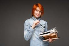 Ritratto della ragazza con i libri sopra fondo grigio Copi la stazione termale Immagini Stock