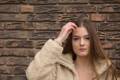 Ritratto della ragazza con il cappotto di inverno accanto al muro di mattoni fotografie stock