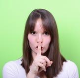 Ritratto della ragazza con il gesto per silenzio contro il backgrou verde Fotografie Stock Libere da Diritti