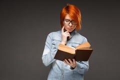 Ritratto della ragazza con il libro sopra fondo grigio Copi la stazione termale Fotografia Stock