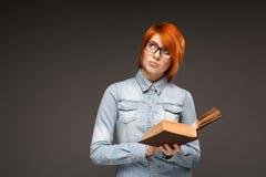 Ritratto della ragazza con il libro sopra fondo grigio Copi Spac Immagini Stock