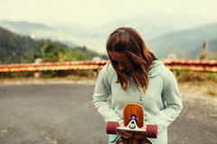 Ritratto della ragazza dei pantaloni a vita bassa con il longboard Immagine Stock