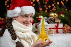 Ritratto della ragazza del bambino con la torre Eiffel e la decorazione di natale, fondo scuro con le luci, espressione del front Immagine Stock Libera da Diritti