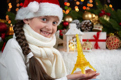 Ritratto della ragazza del bambino con la torre Eiffel e la decorazione di natale, fondo scuro con le luci, espressione del front Fotografia Stock