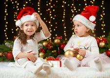 Ritratto della ragazza del bambino in decorazione di natale, emozioni felici, concetto di vacanza invernale, fondo scuro con illu fotografia stock