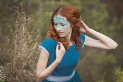 Ritratto della ragazza del redhair nella foresta blu del vestito in primavera Immagine Stock