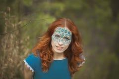 Ritratto della ragazza del redhair nella foresta blu del vestito in primavera Immagini Stock