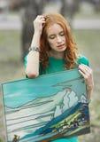 Ritratto della ragazza del redhair in vestito verde con l'affresco in sue mani Fotografie Stock