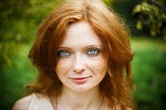 Ritratto della ragazza della testarossa con gli occhi azzurri sulla natura Immagini Stock Libere da Diritti