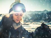 Ritratto della ragazza dello snowboarder sui precedenti dell'alta montagna Immagine Stock