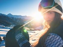Ritratto della ragazza dello snowboarder sui precedenti dell'alta montagna Fotografie Stock