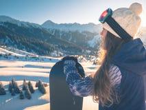 Ritratto della ragazza dello snowboarder sui precedenti dell'alta montagna Immagini Stock Libere da Diritti