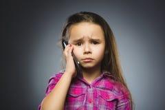 Ritratto della ragazza di offesa con il cellulare o il telefono cellulare Emozione umana negativa fotografie stock