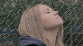 Ritratto della ragazza europea bionda lunatica e triste con il recinto del ferro sui precedenti Giovane donna che getta testa pos archivi video