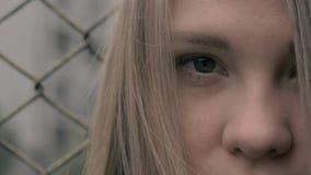 Ritratto della ragazza europea bionda lunatica e triste con il recinto del ferro sui precedenti Giovane donna davanti a metallo archivi video
