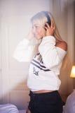 Ritratto della ragazza felice calda con le cuffie che ascolta la musica pop Immagine Stock