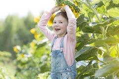 Ritratto della ragazza felice che gioca con il girasole all'azienda agricola immagine stock