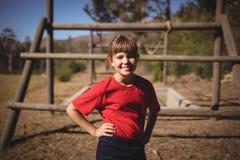Ritratto della ragazza felice che sta con le mani sull'anca durante la corsa ad ostacoli immagine stock libera da diritti