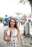 Ritratto della ragazza felice di bello sorriso con la fragola in cioccolato al fondo del parco di divertimenti immagine stock