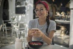 Ritratto della ragazza graziosa con l'intrecciatura e la bandana, avendo resto in caffè di estate immagini stock libere da diritti