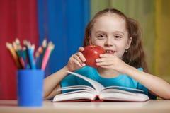 Ritratto della ragazza graziosa felice che tiene una mela rossa nell'aula Immagine Stock