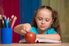 Ritratto della ragazza graziosa felice che tiene una mela rossa nell'aula Fotografie Stock Libere da Diritti