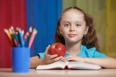 Ritratto della ragazza graziosa felice che tiene una mela rossa nell'aula Immagini Stock Libere da Diritti
