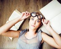 Ritratto della ragazza pazza dello studente in vetri con i libri e il cockroa Fotografia Stock