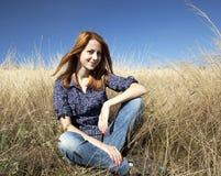 Ritratto della ragazza red-haired felice sull'erba di autunno fotografia stock