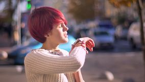 Ritratto della ragazza rosa-dai capelli graziosa emozionale che chiama facendo uso del suo orologio sul fondo vago della via video d archivio