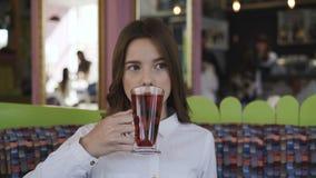 Ritratto della ragazza sicura che beve succo fresco in caffè 4K stock footage