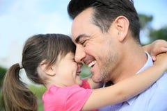 Ritratto della ragazza sorridente che abbraccia suo padre Fotografia Stock Libera da Diritti