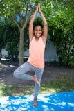 Ritratto della ragazza sorridente che fa yoga di posa dell'albero Immagine Stock