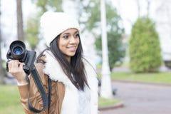 Ritratto della ragazza sorridente con la macchina fotografica professionale, all'aperto. Fotografia Stock